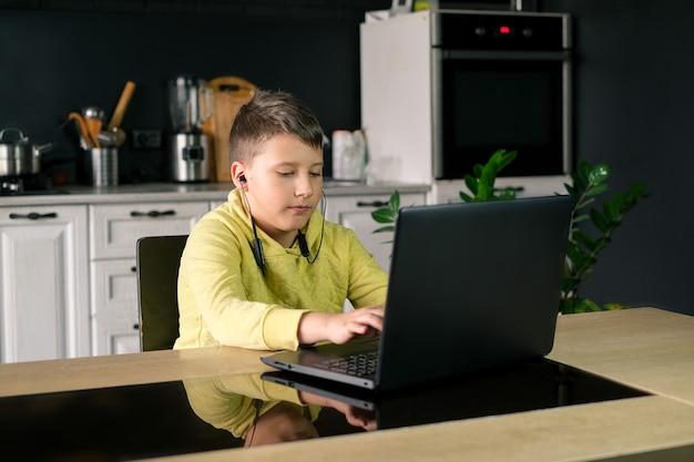 Menino com roupas amarelas assistindo filme estudando ou jogando jogo online no computador na cozinha de casa