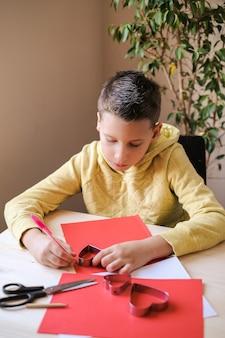 Menino com roupas amarelas fazendo cartão postal de papel com corações para o dia dos namorados