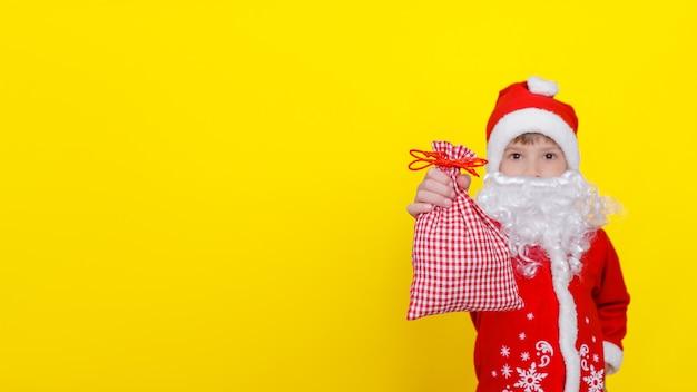 Menino com roupas de papai noel, barba branca mostra saco de presentes no foco seletivo de mão estendida