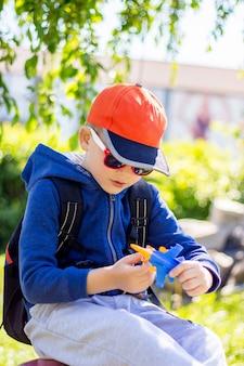 Menino com roupas elegantes é interpretado por um avião de brinquedo