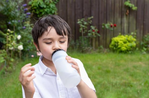 Menino com sede bebendo água potável, menino branco segurando uma garrafa de água