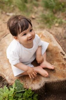 Menino com shortinho branco sentado no toco de uma árvore no parque