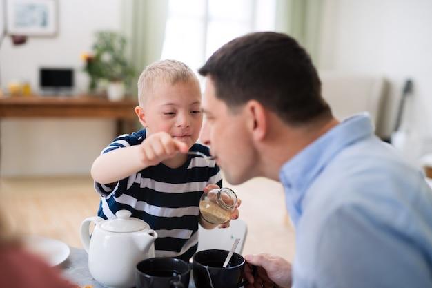 Menino com síndrome de down com o pai à mesa, alimentando o pai ao tomar o café da manhã.