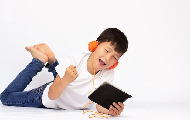 Menino com smartphone e fones de ouvido deitado na superfície branca