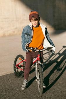 Menino com sua bicicleta ao ar livre na cidade