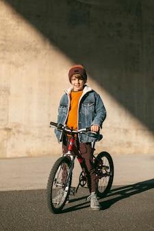 Menino com sua bicicleta lá fora na cidade