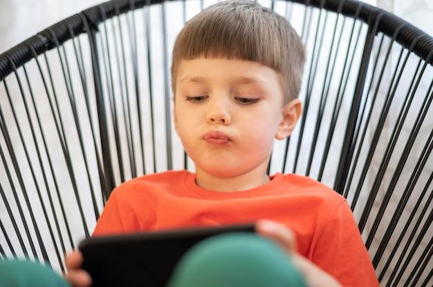 Menino com tablet jogando na cadeira