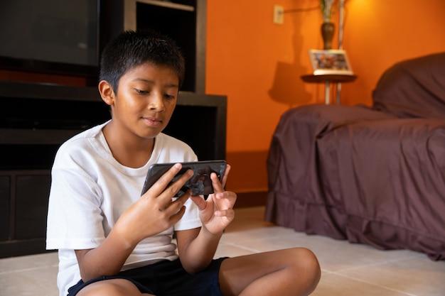 Menino com telefone celular em casa sentado em uma esteira em casa