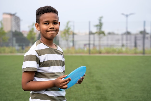 Menino com tiro médio segurando frisbee