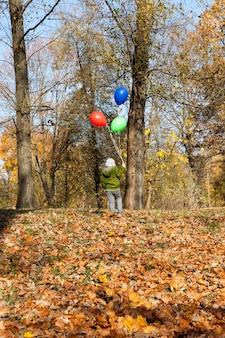 Menino com um balão vermelho verde e azul na temporada de outono