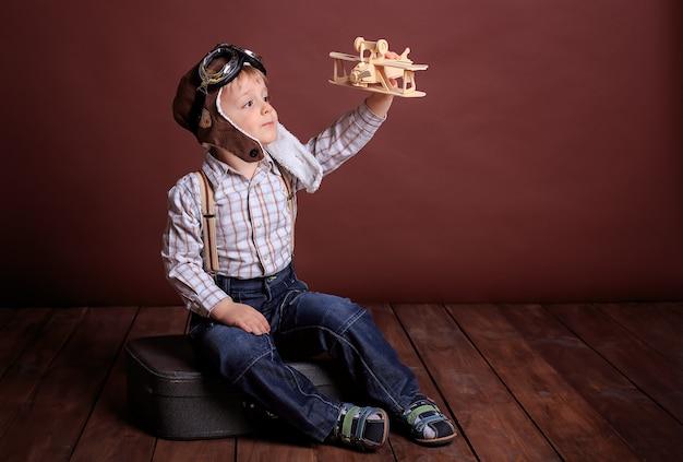 Menino com um capacete brinca com um avião de madeira. o menino sonha em se tornar piloto. feriado dos homens