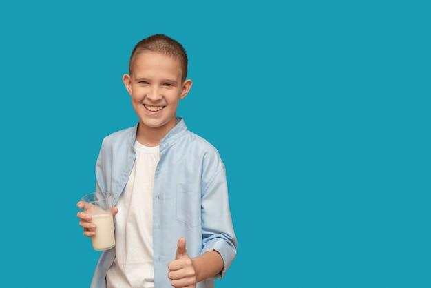 Menino com um copo de leite sorriso feliz sobre um fundo azul. leite no café da manhã.