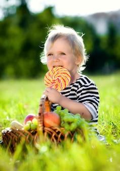 Menino com um doce em uma grama verde