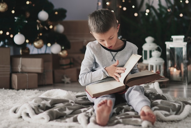 Menino com um livro mágico no chão