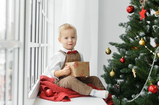 Menino com um presente nas mãos, sentado perto da árvore de natal e olhando para a câmera. férias, presente e conceito de ano novo