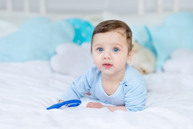 Menino com um roedor para a dentição ou um chocalho na cama para dormir, um bebezinho saudável e feliz em um macacão azul brincando