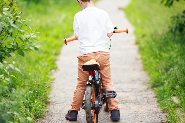 Menino com uma bicicleta na rua