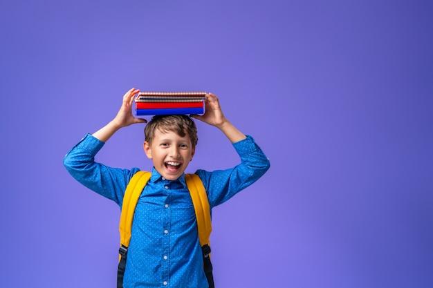 Menino com uma camisa com cadernos na cabeça