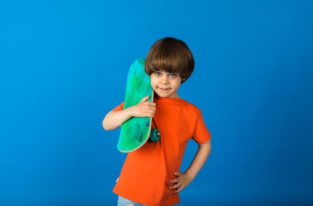 Menino com uma camiseta laranja segurando um skate em uma superfície azul com espaço para texto