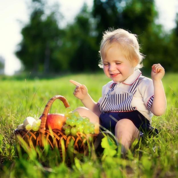 Menino com uma cesta de frutas senta-se em uma grama