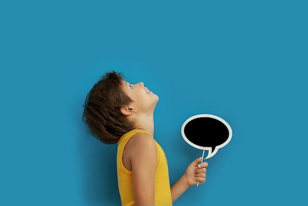 Menino com uma lousa vazia para o texto em mãos em uma parede azul