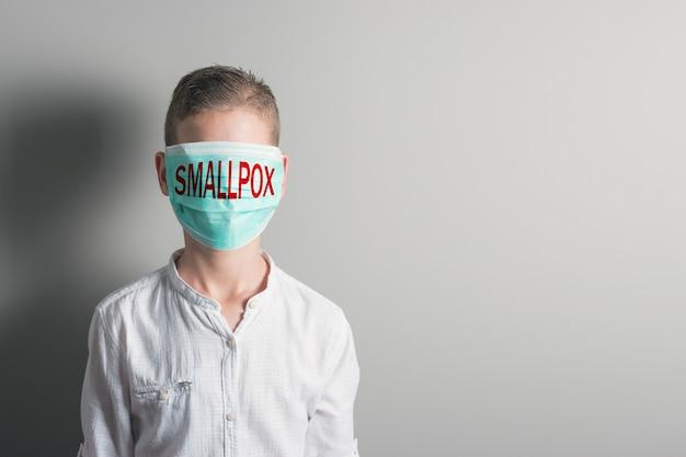 Menino com uma máscara médica com a inscrição vermelha cocaína no rosto no fundo brilhante.