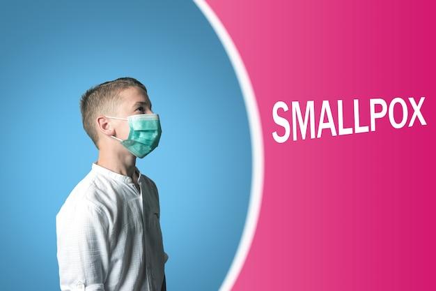Menino com uma máscara médica em um fundo brilhante com a inscrição smallpox