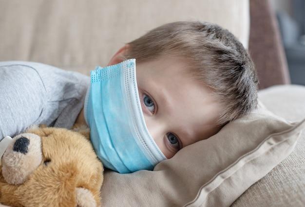 Menino com uma máscara médica em um sofá com um ursinho de pelúcia