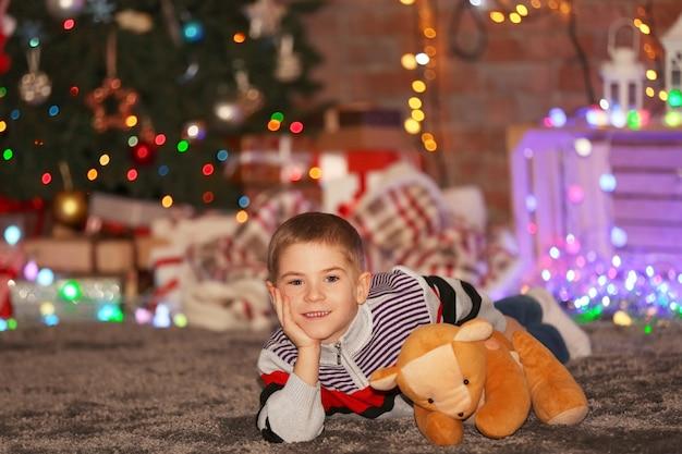 Menino com ursinho de pelúcia em uma sala de natal decorada