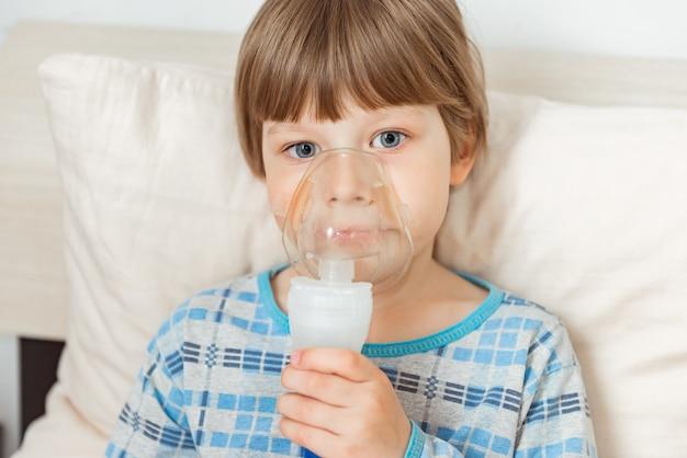 Menino com vírus sincicial respiratório, inalando medicamento por meio de uma máscara de inalação. gripe, conceito de coronavírus