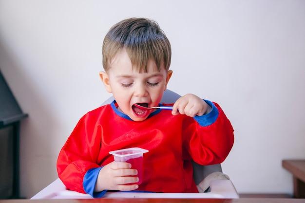 Menino começando a comer sozinho, sem a ajuda dos pais. família e conceito de dieta saudável.