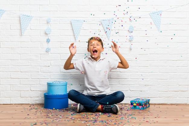 Menino comemorando seu aniversário com confetes em uma festa