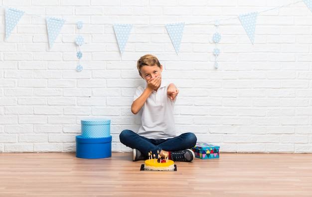 Menino comemorando seu aniversário com um bolo apontando com o dedo para alguém e rindo muito