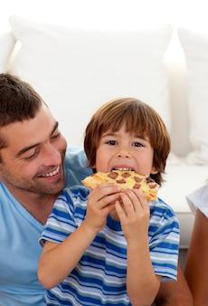 Menino comendo pizza na sala de estar com seu pai