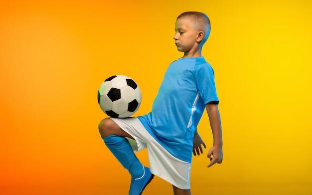 Menino como um jogador de futebol em roupas esportivas, praticando em uma parede gradiente amarela em néon