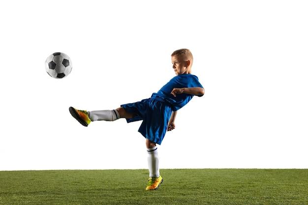 Menino como um jogador de futebol ou futebol americano em roupas esportivas, fazendo uma finta ou um chute com a bola para um gol em branco.