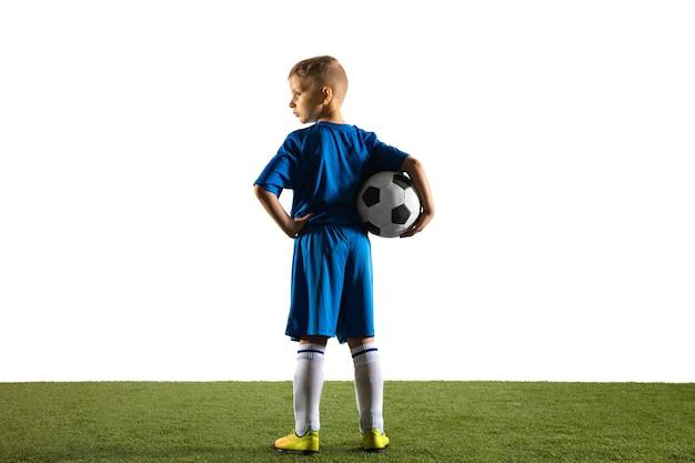 Menino como um jogador de futebol ou futebol americano em sportswear em pé com a bola como um vencedor, o melhor atacante ou goleiro na parede branca. ajuste o menino brincando em ação, movimento, movimento no jogo.