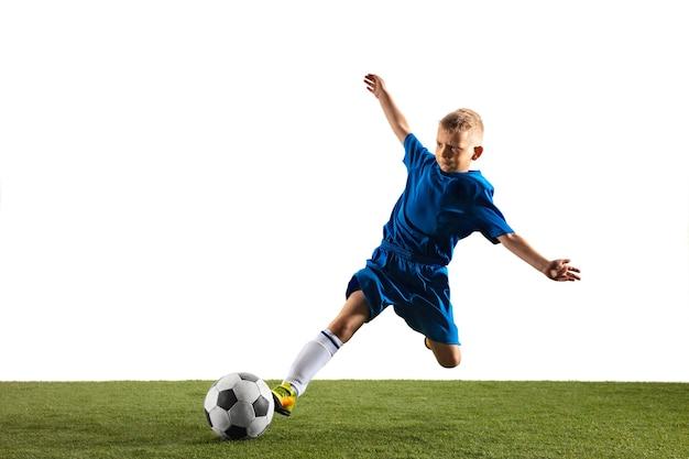 Menino como um jogador de futebol ou futebol americano no sportwear, fazendo uma finta ou um chute com a bola para um gol no fundo branco do estúdio. ajuste o menino brincando em ação, movimento, movimento no jogo.