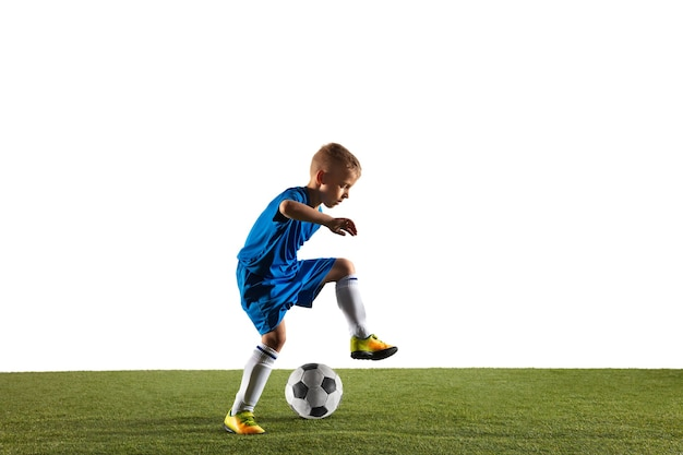 Menino como um jogador de futebol ou futebol americano no sportwear, fazendo uma finta ou um chute com a bola para um gol no fundo branco.