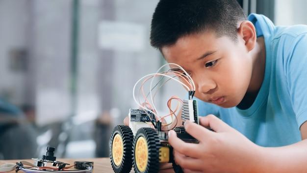 Menino concentrado criando robô no laboratório.
