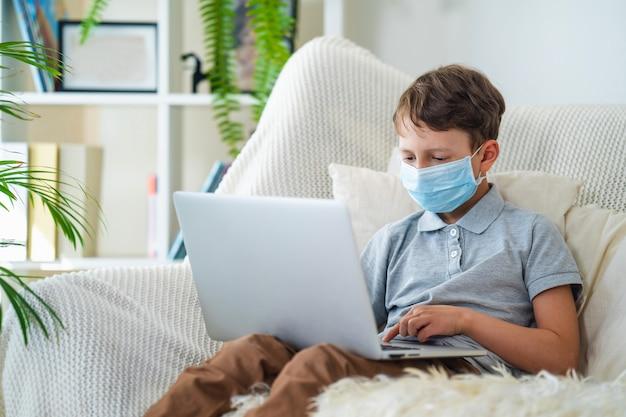 Menino concentrado na máscara com um laptop durante a quarentena. Foto Premium