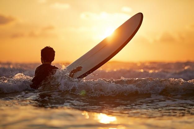 Menino confiante carregando prancha de surf em pé na beira-mar no pôr do sol