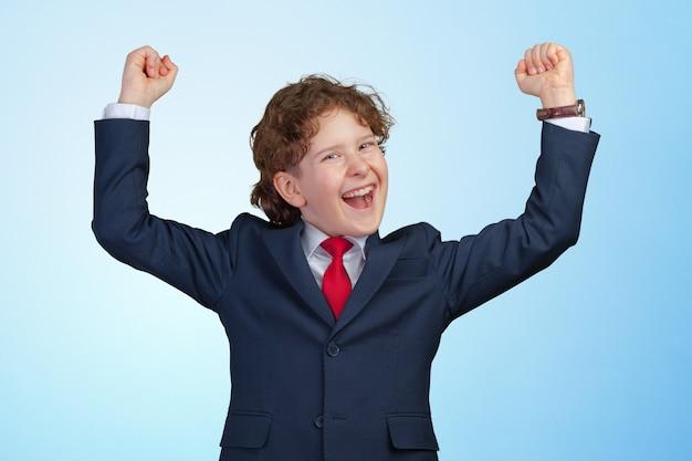 Menino confiante com os punhos erguidos, comemorando um sucesso recente