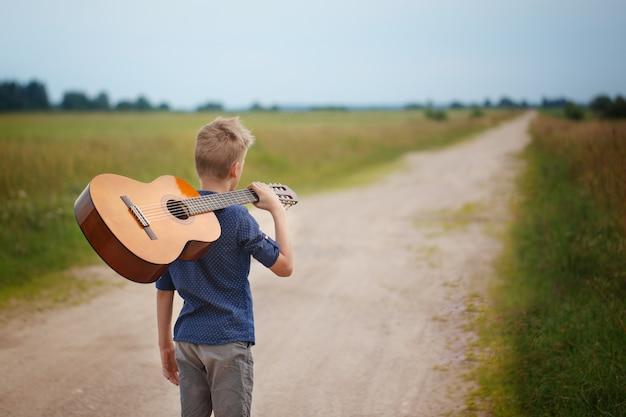 Menino considerável com guitarra que anda na estrada no dia de verão. vista traseira