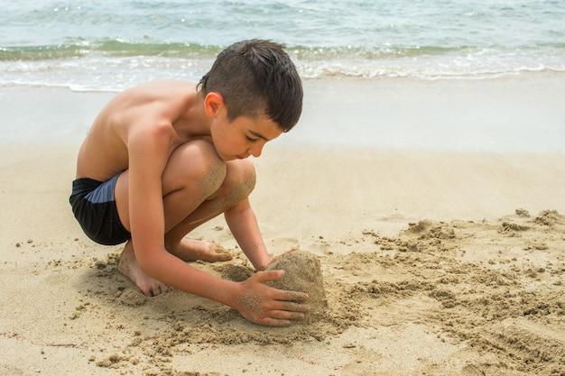 Menino constrói um castelo de areia na praia à beira-mar