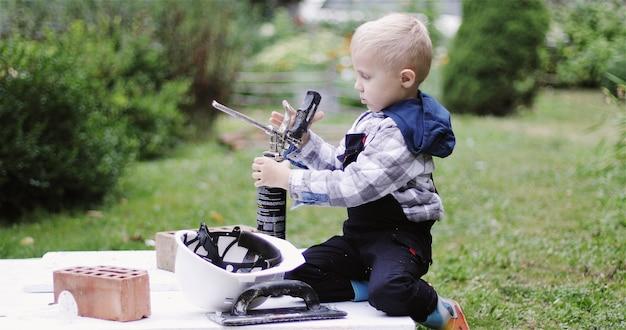 Menino construtor brincando com um cilindro de espuma de poliuretano