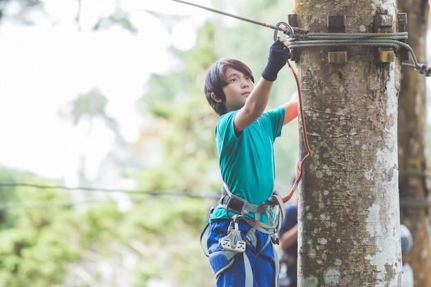 Menino corajoso ativo, desfrutando de escalada de saída no parque de aventura no topo da árvore
