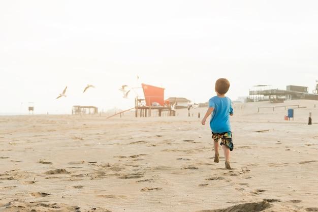 Menino correndo na costa de areia com construções