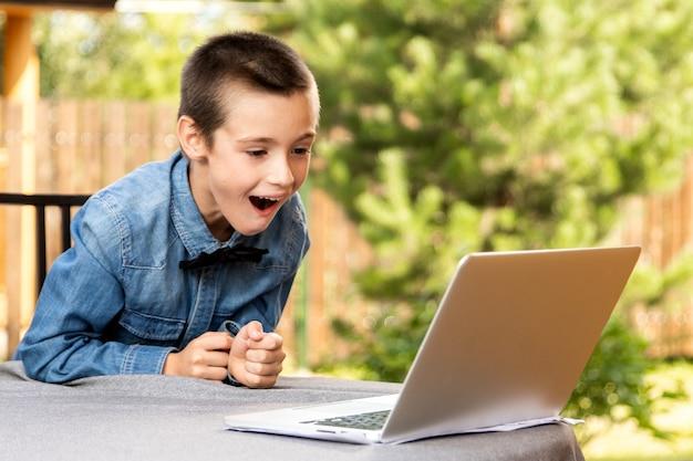 Menino criança alegremente surpreendente, está usando um laptop e se comunica pela internet em casa. ensino doméstico, aprendizagem à distância, online e