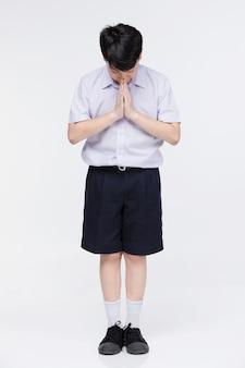 Menino criança asiática no uniforme do estudante, agindo sawaddee significa olá.